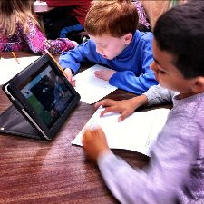 Students in a classroom with an iPad