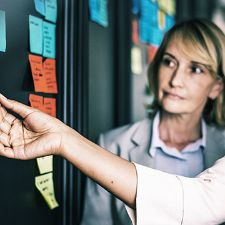 Woman looking at Post-It notes in an office