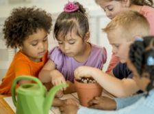 Children tending to a potted plant