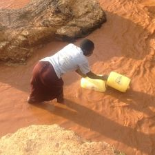 Person gathering water in a dirty river