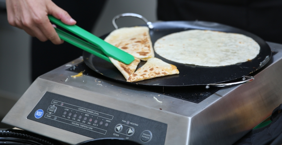 SCE induction cookware flipping a quesadilla