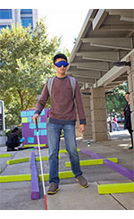 Picture of individual blindfolded using cane through mobility maze