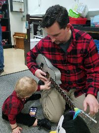 BEGIN child Everett helps his dad strum a toy guitar.  They are wearing matching festive red and black flannel shirts.