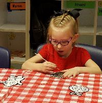 STARS student Hilde sits at a table and paints an ornament.