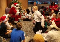 STARS student Elizabeth reaches for her present from Santa as the other students wait their turn.