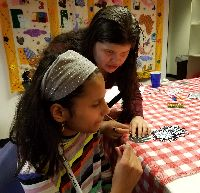 STARS student Raveena works on a craft at a table with her instructor, Aracely.