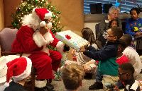 STARS student Kyler reaches to receive his gift from Santa.