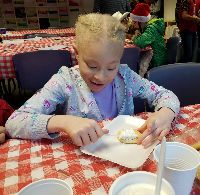 STARS student Takaria sits at a table to ice a cookie.  She is wearing a purple outfit and is smiling.