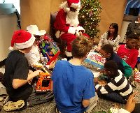 Under the watchful eye of Santa, a group of STARS boys sit in the floor and compare their presents after tearing off the wrapping paper.