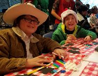 STARS students Aidan and Terry sit at a table together to work on their craft projects.  Aidan is wearing a white cowboy hat and Terry is wearing a red Santa hat.
