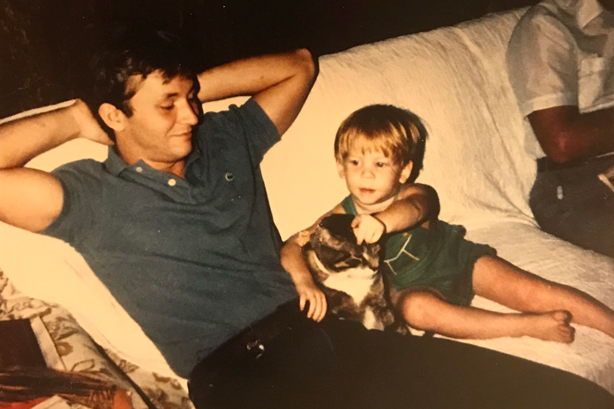 In what is clearly an old candid photo from the 1980s, a man and boy sit together on a white couch.