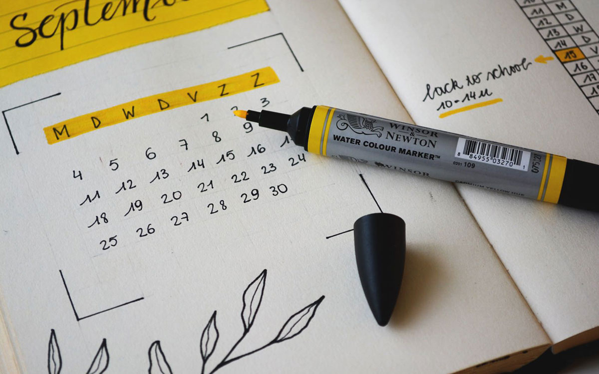 A yellow marker sitting on an open notebook with a hand-drawn calendar.