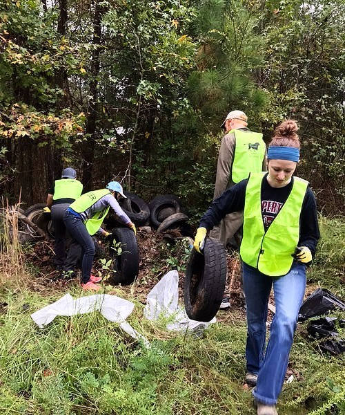 Volunteers in vests pulling left behind tires from the forest