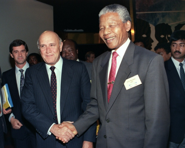 Nelson Mandela shakes hands with South Africas president Frederik W de Klerk, who he succeeded, in 1992. Photo courtesy The Scotsman.