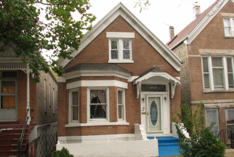 gabled brick workers cottage with bay window, blue stairs, and white trim