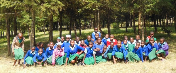 Children in front of trees planted with funding from CHASE Africa