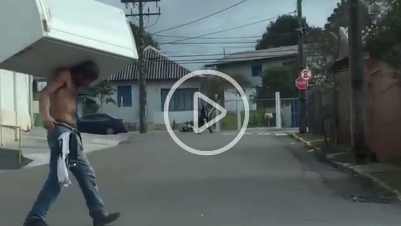 Man walking across the road with a fridge - click to play video