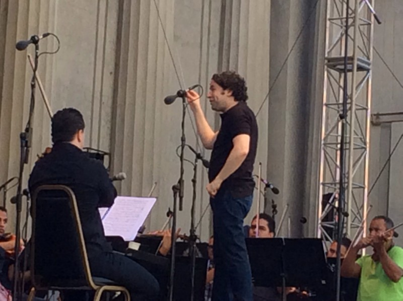 Photograph of Maestro Gustavo Dudamel ont he podium during rehearsal with the SF Girls Chorus and the Simon Bolivar Symphony Orchestra of Venezuela