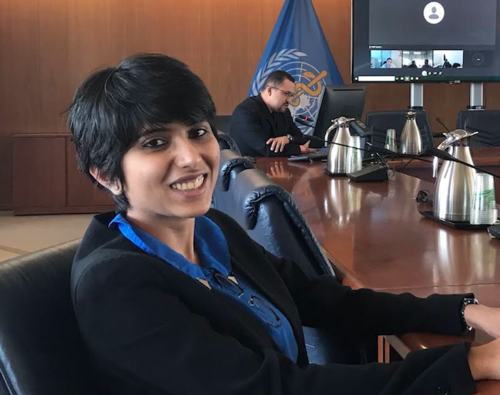 Headshot of Harshala Chandraiah, pictured seated at UN conference table.