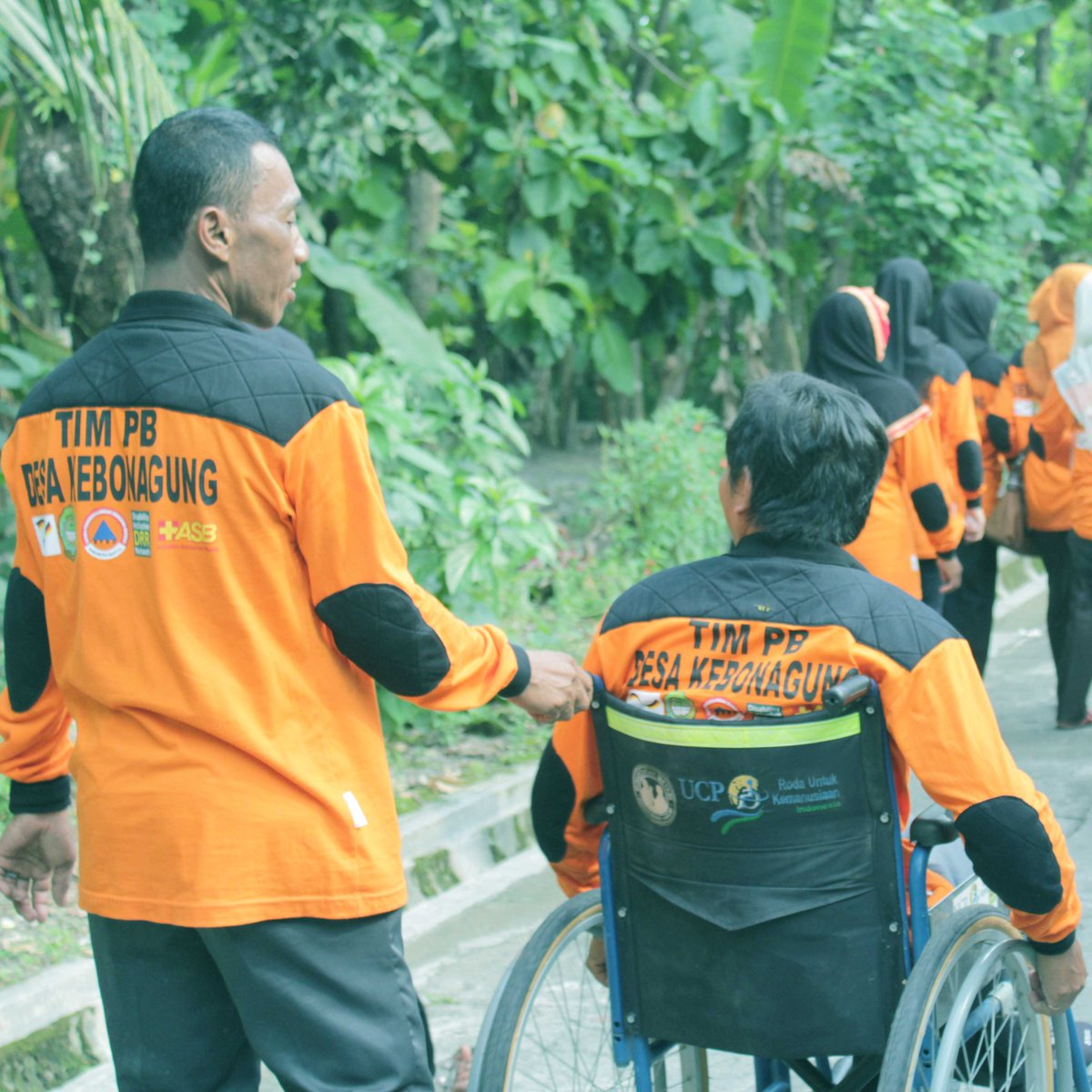 Two disaster management volunteers photographed from behind, one of whom is using a wheelchair.