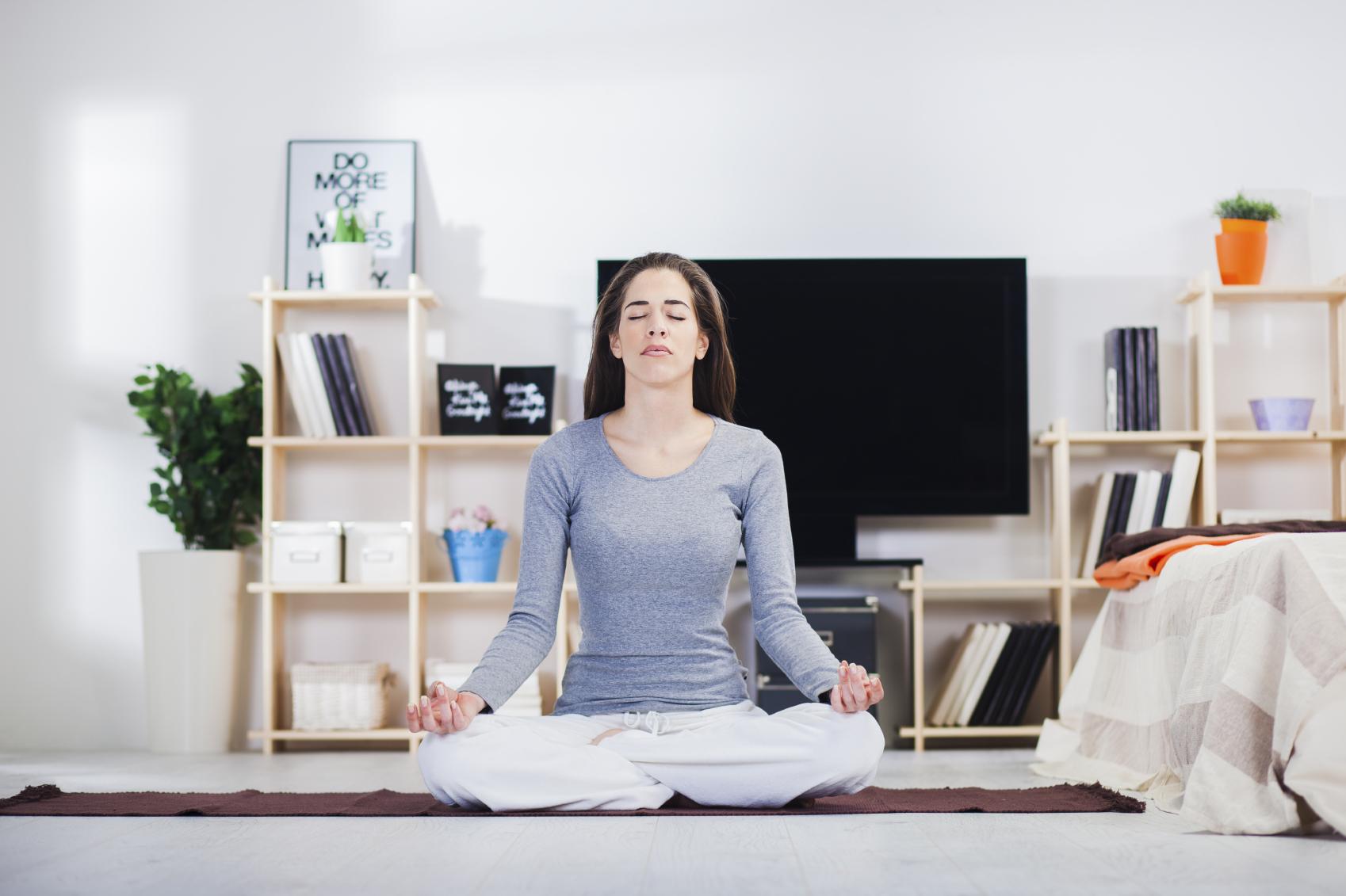 kvinde-laver-yoga-hjemme-i-stuen