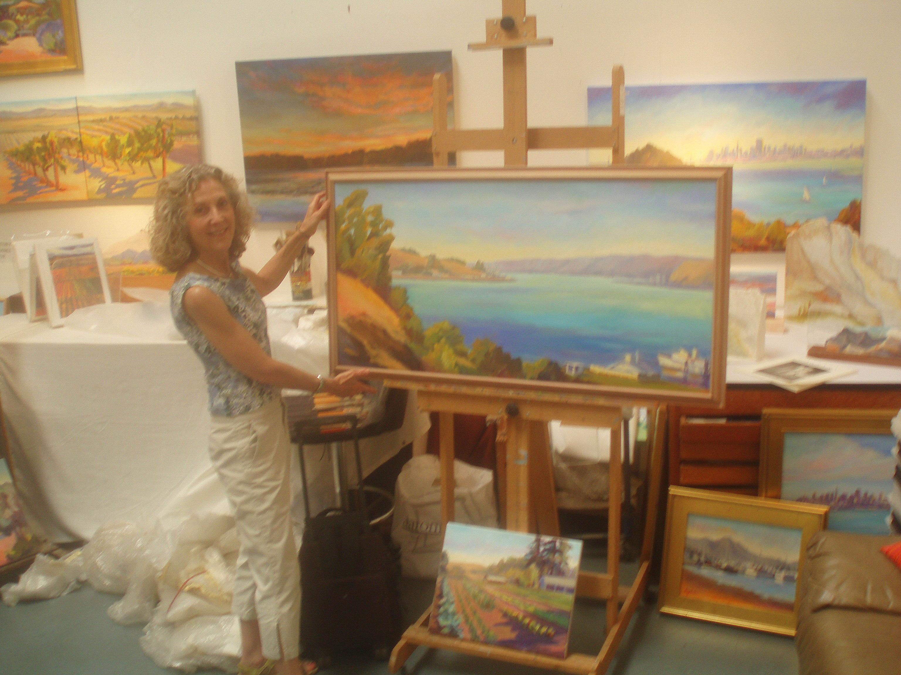 Artist showing off large landscape at her easel