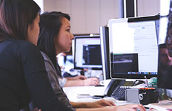 two women working at computer together in office
