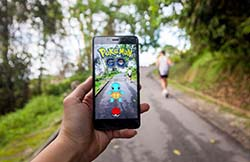 hand holding smartphone playing pokemon go