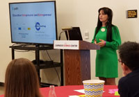 Woman standing behind a podium giving a presentation