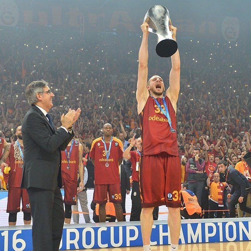 Carroll basketball alum Sinan Guler '06 holding trophy