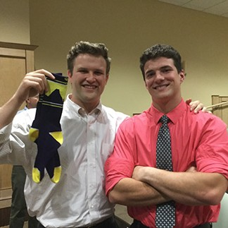 Two Carroll College students, one holding a ribbon award.
