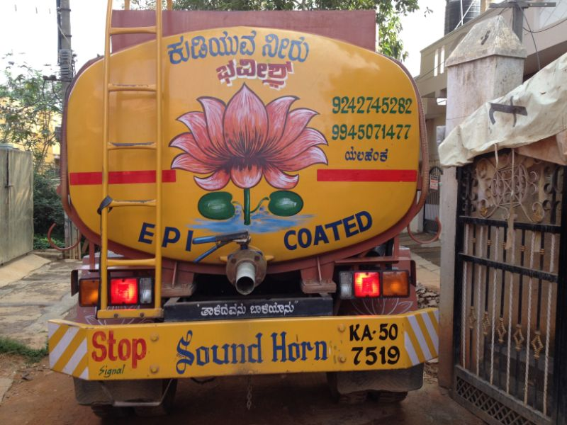 Back of a yellow water tanker decorated with a pink and green flower