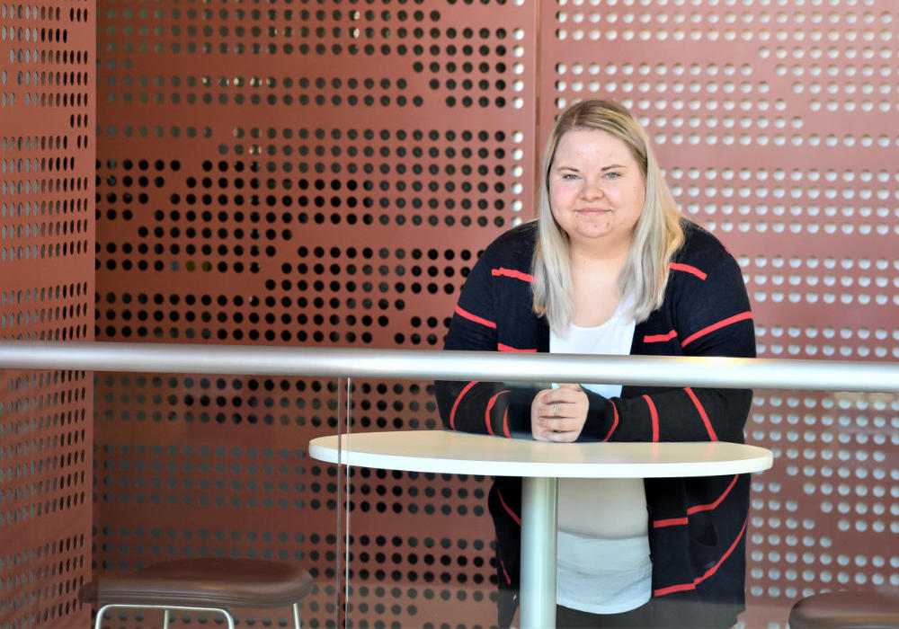 Kyra Sims leans against a table in the Integrated Research and Innovation Center