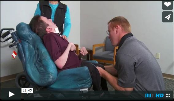 A man is getting fitted for a wheelchair with molded supports. Image is a link to a video about CRT.