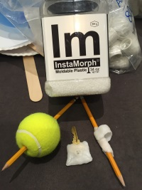 Shows a pencil pierced through a tennis ball, a key augmented with moldable plastic, and a pencil augmented with moldable plastic.