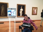 Robot with image of man next to man seated in power wheelchair, both in museum gallery