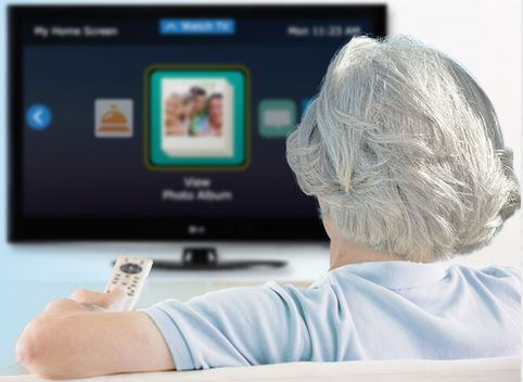 Woman with remote in front of T.V. with interactive screen displayed.