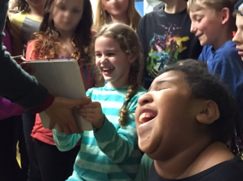 Girl smiles brightly at and holding iPad display surrounded by smiling classmates