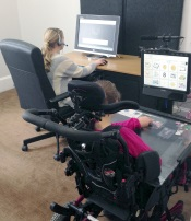 Two young girls seated in front of computer monitors. One wears a headset. One uses a power chair.