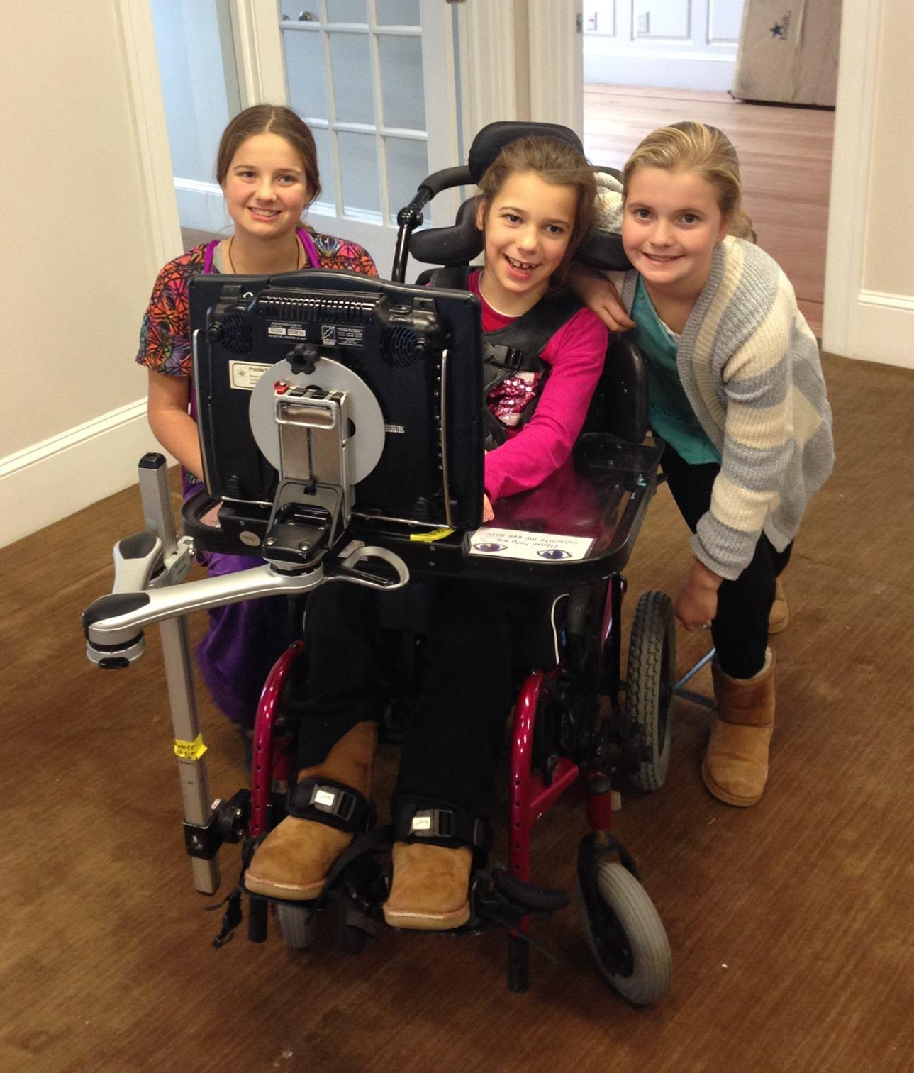 A young girl smiles seated in her powerchair facing a monitor and flanked by her two sisters, also smiling.