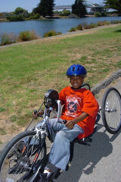African-American boy using a hand tricycle.