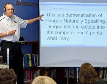 "A man wearing a headset is speaking in front of a class and pointing to a screen with the following text, ""This is a demonstration of Dragon Naturally Speaking. Dragon lets me dictate into the computer and it prints what I say."""