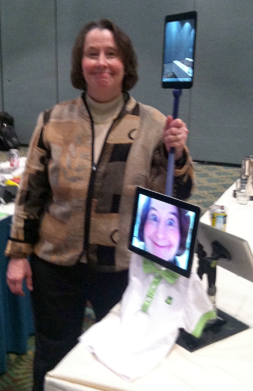 Photo of Dr. Willkomm smiling with an iPads mounted on stands, including one displaying a photo of her smiling face above an empty polo shirt.