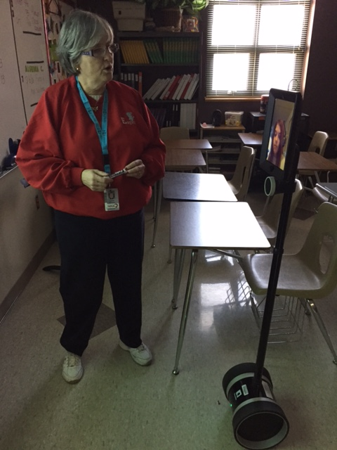 A teacher at the front of the classroom speaks to a young woman displayed on an iPad mounted on wheels (a Double2 Robot)