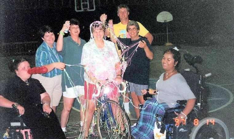 Photo of Liz and another camper in a power chair goofing around with counselors draped in silly string.