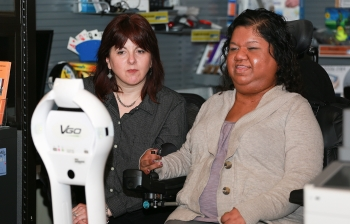 Two women looking at the VGo display, both seated, one in a power wheelchair holds a joystick.