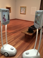 Two robots facing each other in a museum gallery