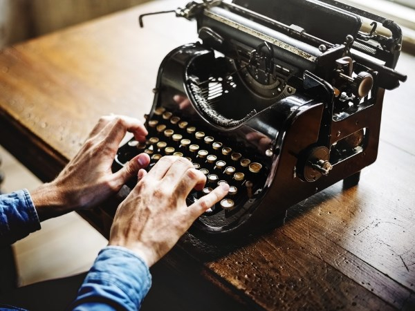A photo of a person using an old-fashioned typewriter.