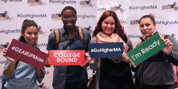 "Four GEAR UP students pose in a photo booth with signs reading ""#GEARUPMass,"" ""COLLEGE BOUND,"" ""#GoHigherMA,"" and ""I'm Ready"""