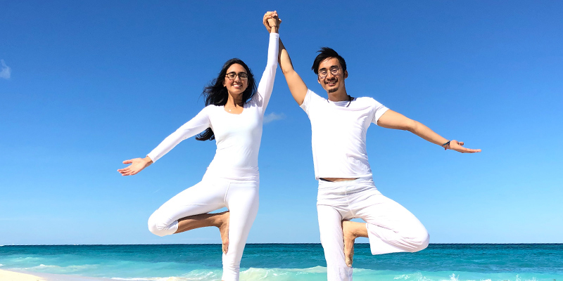 Happy couple doing yoga together on the beach